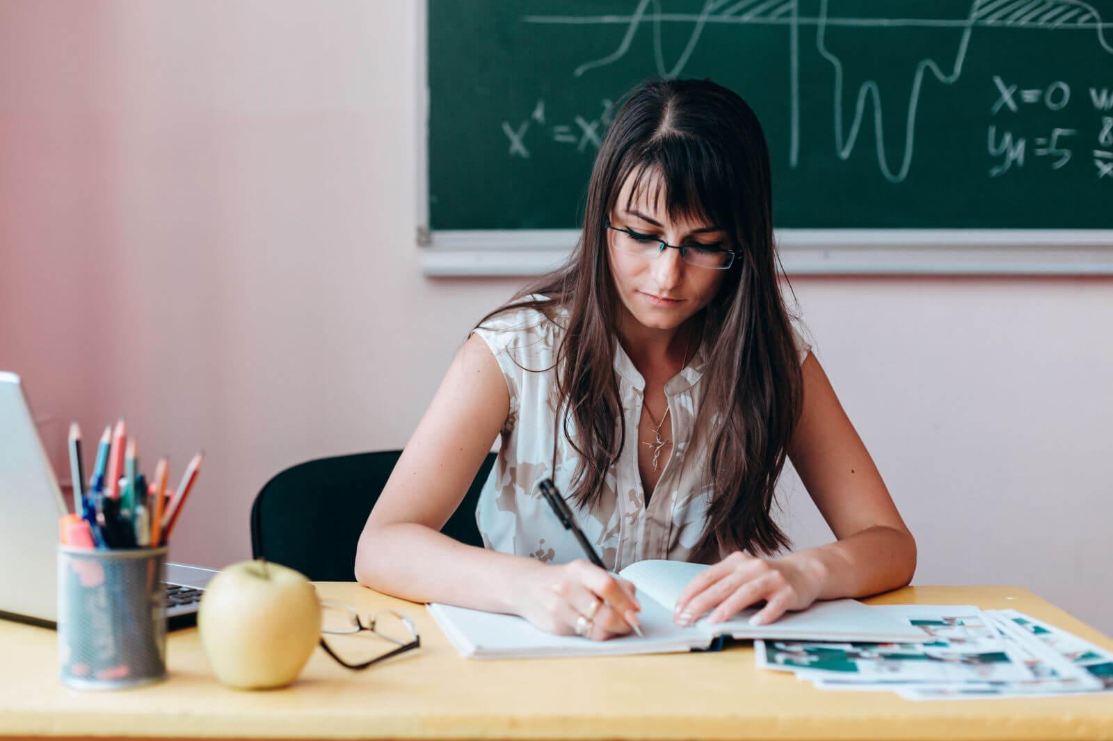 Nauczyciel uzupełnia dziennik lekcyjny